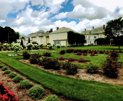A View Of The Back Of The Yellow Mansion Of Wistariahurst, Looking Across Bloomnig Formal Gardens