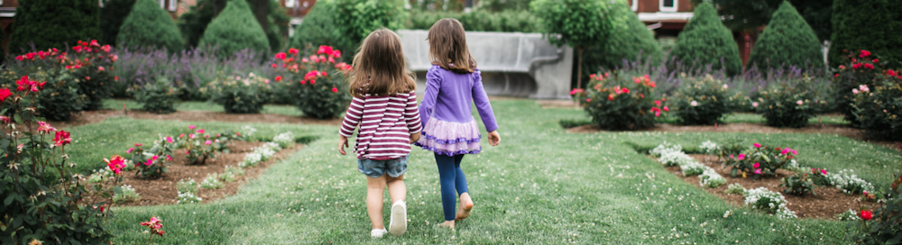 two toddler girls walking handing in hand on a lawn