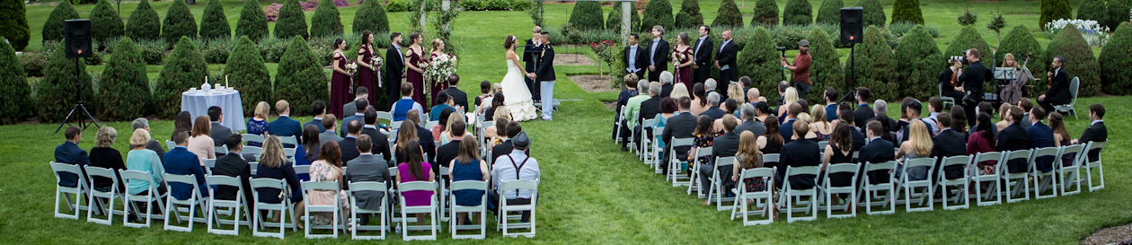an aerial view of audience in white chairs in a garden watching a bride and groom hold hands