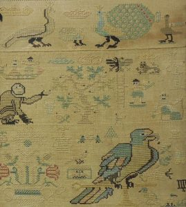 image of antique cross-stitched sampler with peacocks, a monkey, a tree, flowers, people and a parrot