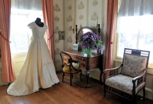 a victorian era bedroom setting with a white, pleated wedding dress on a mannequin. A dressing table with purple flowers and an upholstered chair are also in the frame.