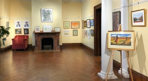 a yellow gallery room with pantings on the walls, easels, and over a fireplace