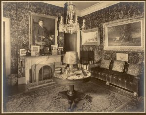 the corner of an ornate room, with a crystal chandelier, leather wall coverings, and a portrait over a marble fireplace