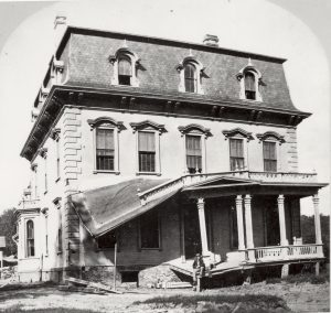 a black and white photo of a three story victorian house that has a damaged and collapsing porch