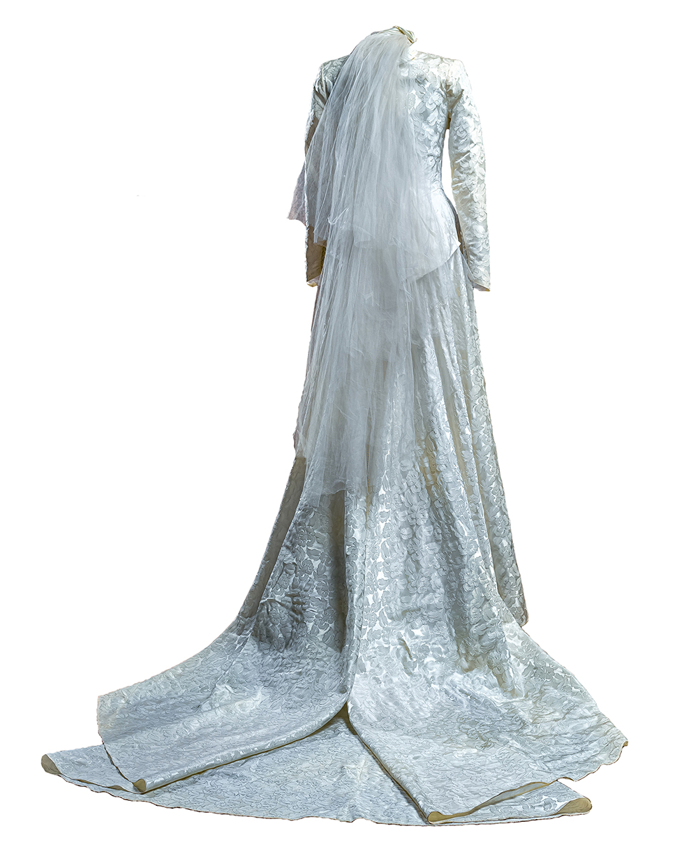 Back of Jacquard leaf-patterned, ivory, Skinner satin wedding gown with three quarter length veil and train