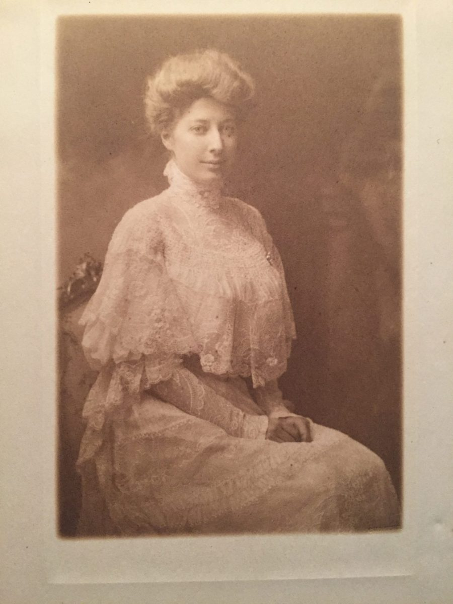 pearl coburn sits with hands in lap, with her lace gown draped around her.