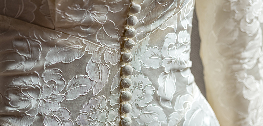 a close up of the back of a white silk wedding dress. The silk has a floral lace overlay and a row of small buttons running up the back