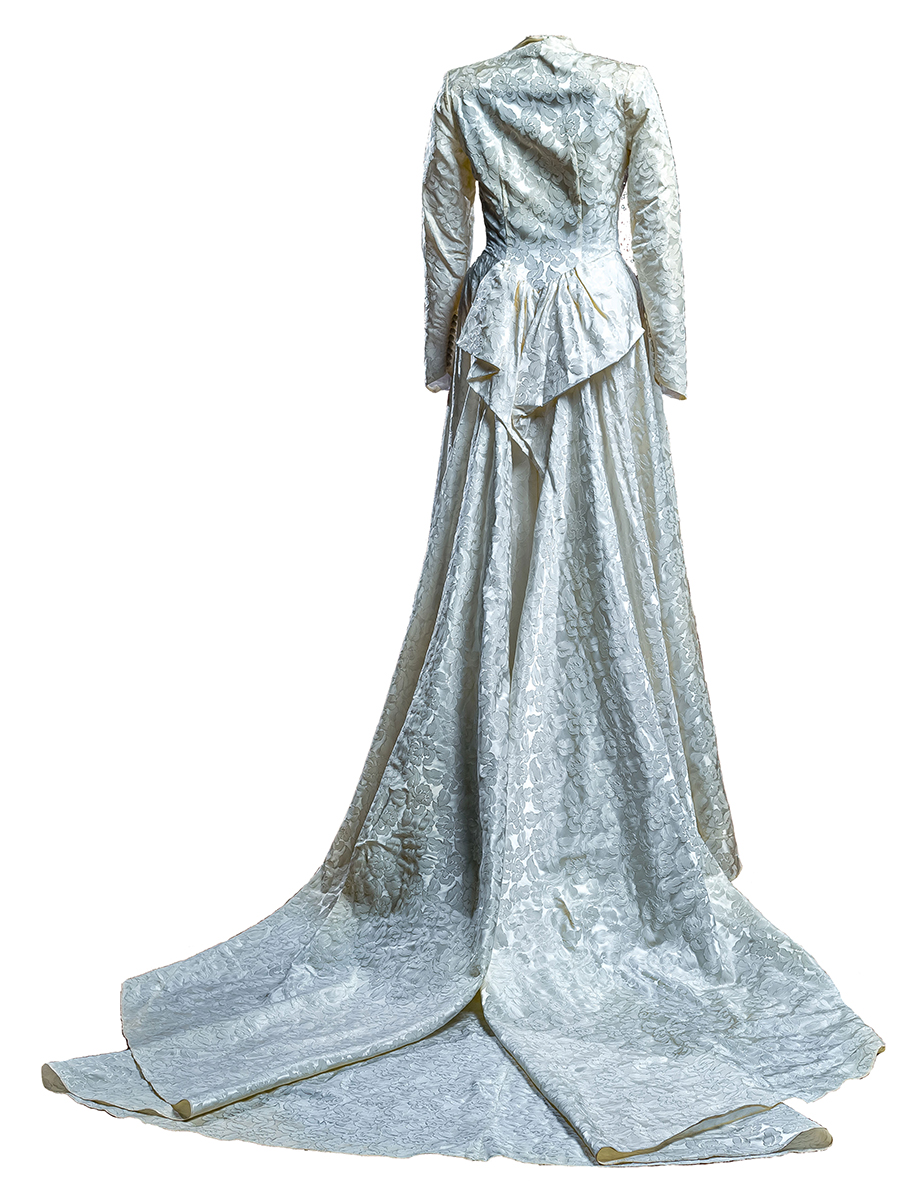 Back of a Jacquard leaf-patterned, ivory, Skinner satin wedding gown train, exaggerated bustle at back.