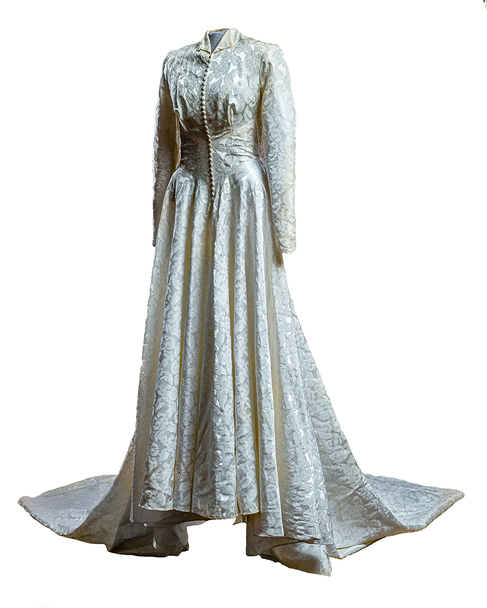 Jacquard leaf-patterned, ivory, Skinner satin wedding gown with covered buttons down front center, train, exaggerated bustle at back.