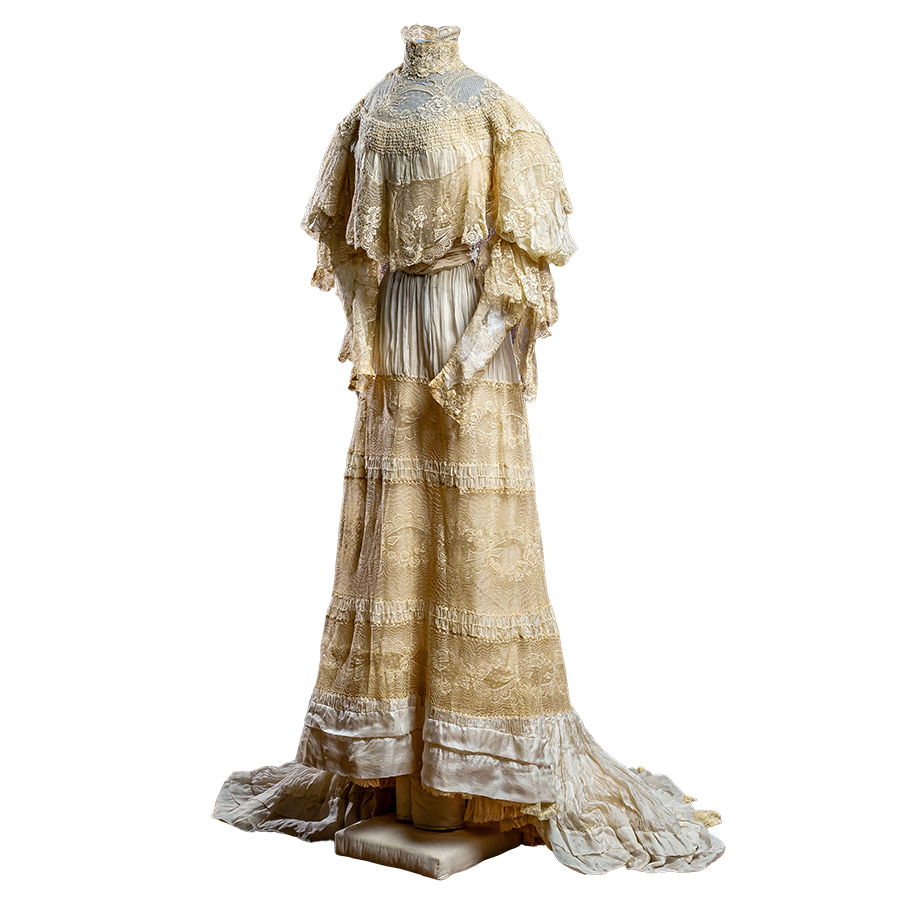 Accordion pleated white silk chiffon gown with exquisite French lace. Lace covers the bodice, neckline, skirt, train and makes up the long, buttoned cuffs. Shoes, stockings and extra ribbons.
