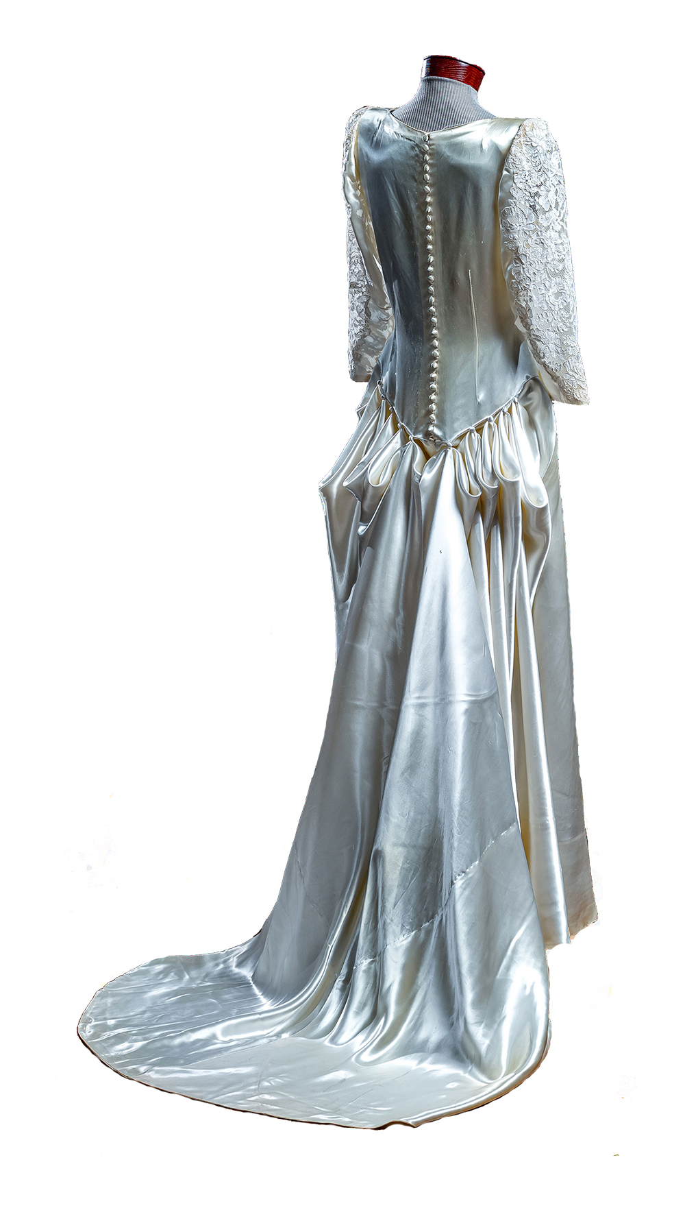 the back of a long-sleeved white dress, with a rippling silk train bustled at the waist, trailing to the floor.
