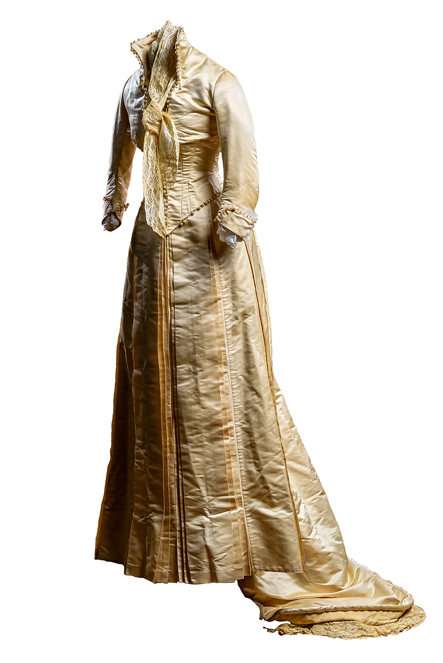 Fitted jacket tapers to pointed, bottom edged with pearls; boned tiara collar and square neckline trimmed with pearls; long sleeves have split cuffs edged with pearls; lace scarf is sewn in at the neck. Skirt has front pleats and a thick layer of pleats in back that form the bustle; the attached long train is trimmed with lace at edges.