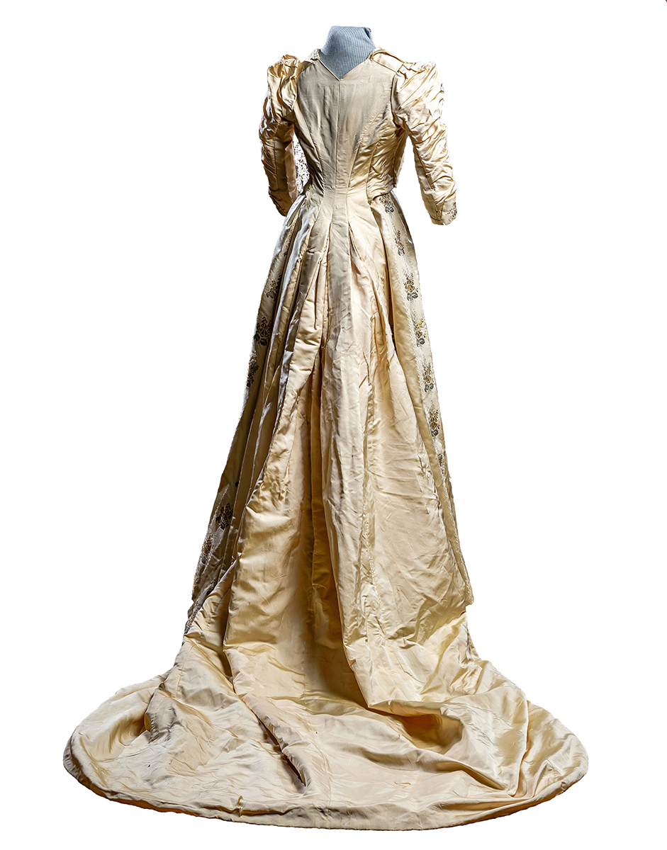 back of Ivory faille fabric wedding gown decorated with stripes of floral satin brocade done in silver and gold metallic threads. Train has wide bands of lace and net ruffles. Sewn in waist cummerbund and 3/4 length ruffled sleeves.