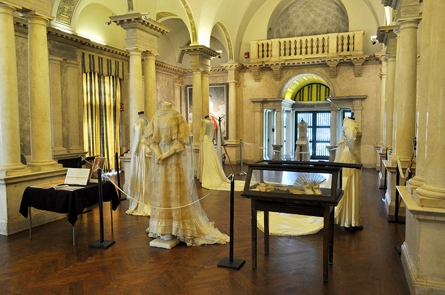 A Long View Of A Wedding Gown Exhibit In An Ornate White Room With Columns And Arched Ceilings. Display Cases And A Lacey Gown In The Foreground