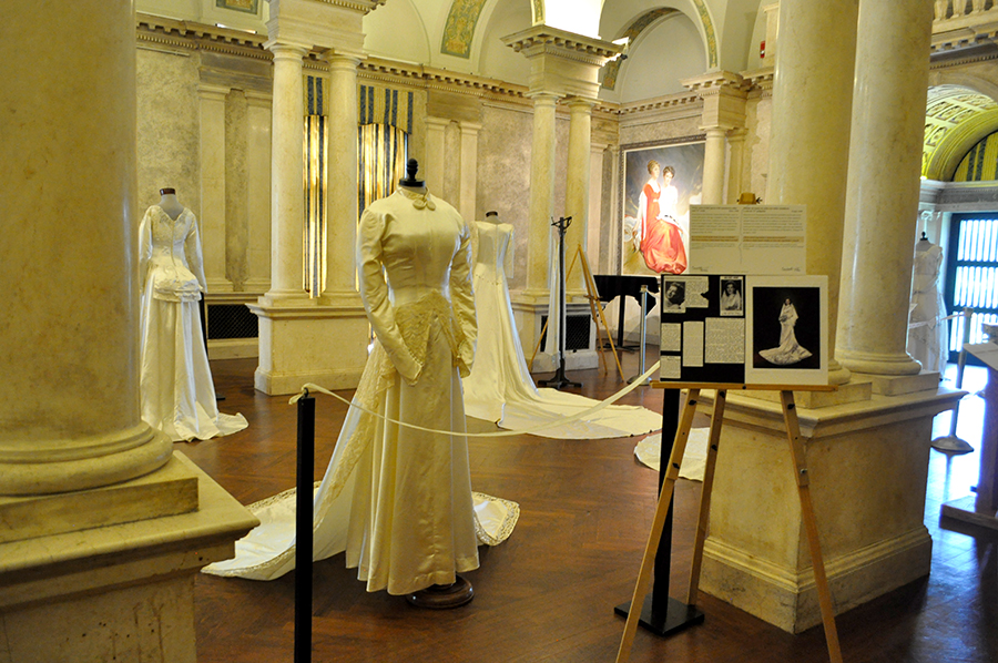 A Wide View Of The Historic Music Room With Dresses And Columns, And Belle And Katharine Portrait In The Background