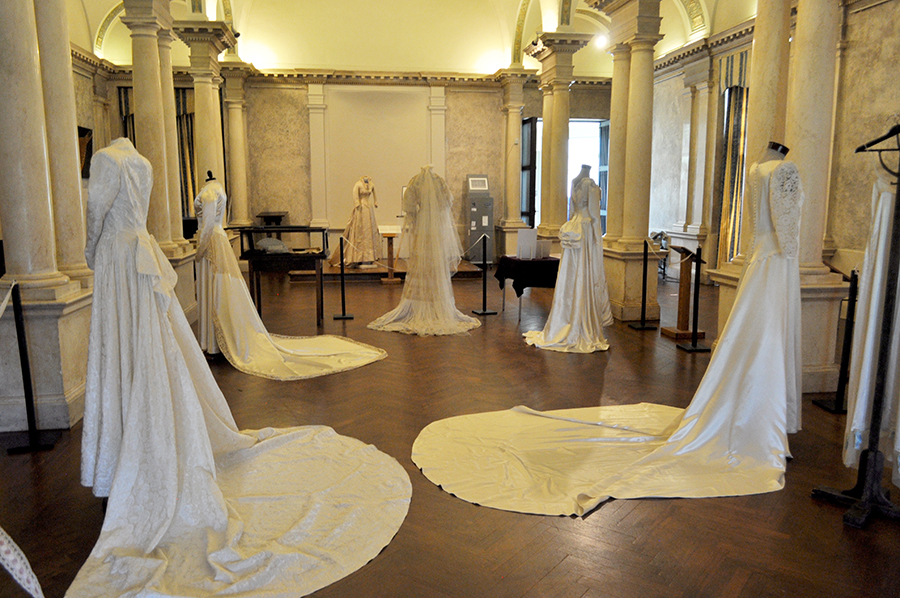Looking Down A Long White Room With Columns At The Trains And Backs Of Several Styles Of Wedding Dresses, Some With Long Sleeves, Bustles, And At The End One With A Long Cathedral Length Veil