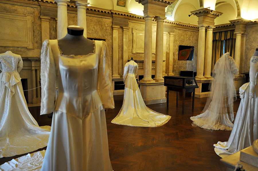 A Gran Room With High Columns And Dramatic Uplight Holds Several Wedding Gowns With Long Train. In The Foregound Is A Silk Gown With A Square Collar And Slightly Puffed Long Sleeves