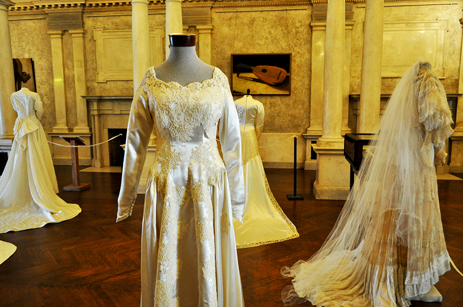 A White Gown With A Lace Collar Is In The Foreground Of A Photo Of Several Wedding Dresses In A Grand Room With Columns. A Painting Of A Lyre Is In The Background On The Wall