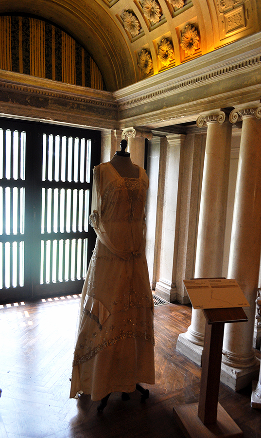 A Floor Length Layered Lace Gown In An Arched Alcove With Dim Light And Columns