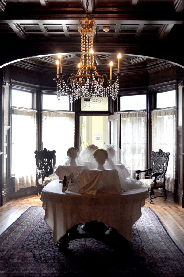 A View Of A Grand Dining Room With Wedding Veils On Display Heads And A Pair Of Wedding Shoes Propped In The Front Of The Display. Ornate Chairs Are Iin The Background And A Chanedeloer Glows Above