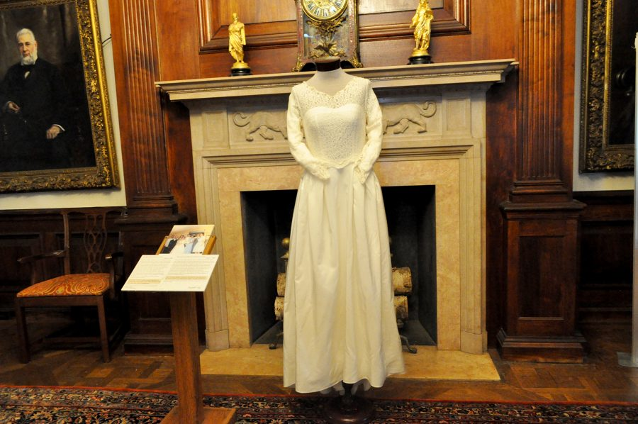 A White, Long-sleeved, Floor-length Wedding Gown Is On Display In Front Of A White Marble Fireplace, Small Gold Statuettes On The Mantle, And A Framed Portrait Off To The Side Staring At The Camera.