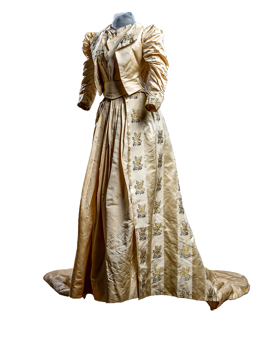 Ivory faille fabric decorated with stripes of floral satin brocade done in silver and gold metallic threads. Train has wide bands of lace and net ruffles. Sewn in waist cummerbund and 3/4 length ruffled sleeves.