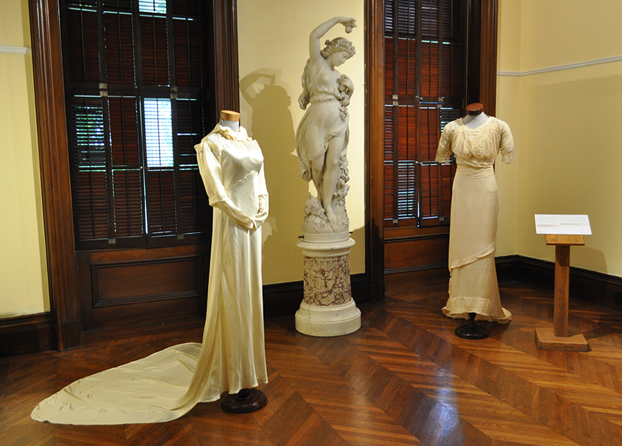 Two White Wedding Gowns, One With A Long Train And One Floor Length, On Either Side Of A Marble Statue Of A Greek Woman Frolicking With Grapes. Yellow Walls And Wooden Shuttered Windows In The Background