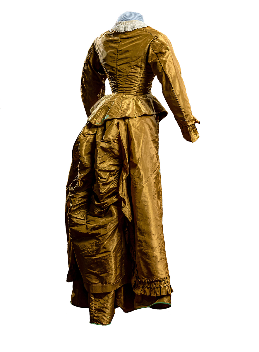 Fitted, boned bodice jacket with lace-covered green buttons; white collar with embroidery and cut work; waxed wool underskirt with full bustle, modified train and green trim at hem. Overskirt with a train and gathers in back to emphasize bustle effect. Ruffles at hem and cuffs.