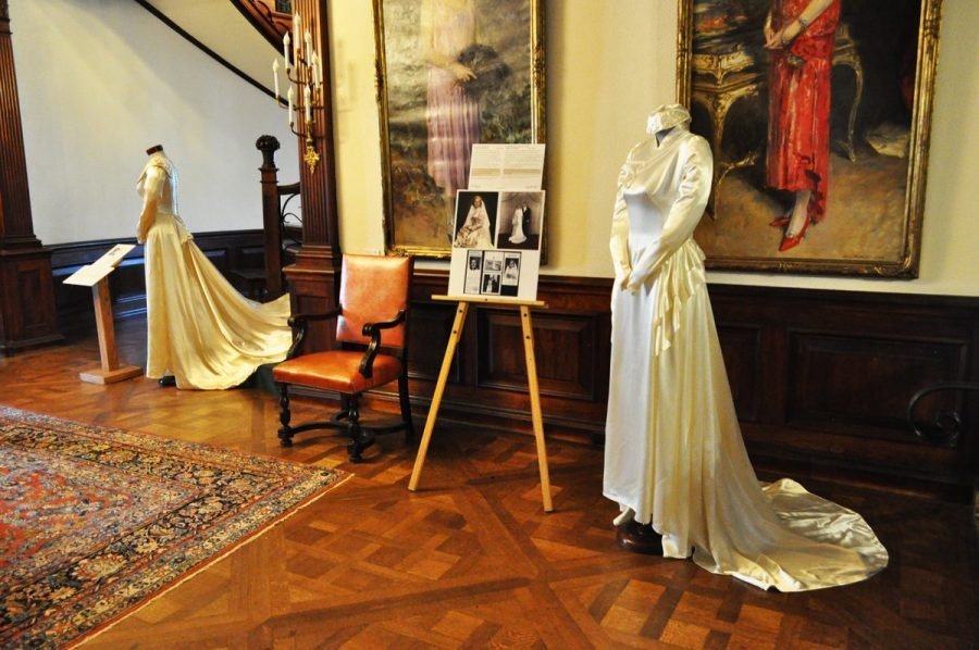 In The Foreground A White Silk Wedding Gown Is On Display, Sleeves Pinned As If Hands Held In Front And In The Backgrounda Second Ivory Gown With A Long Train Can Be Viewed