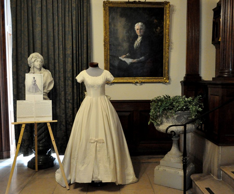 A Floor-lenght White Wedding Gown With Short Sleeves And A Poofed Out Pricess Skirt Is On Display In Front Of A Portrait Of An Older Woman, An Urn Full Of Ivy, A Marble Bust, And A Green Curtain