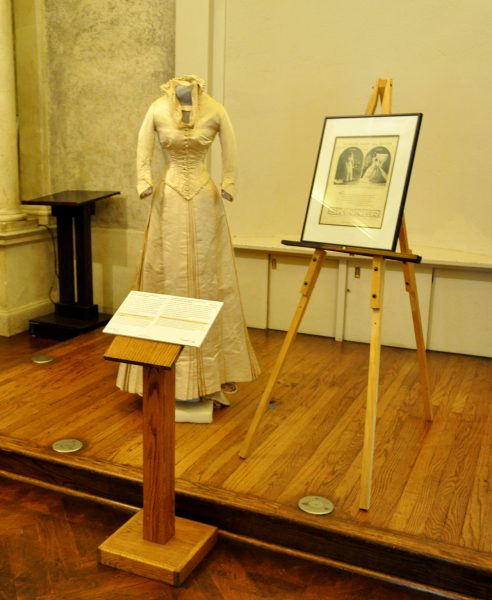 An Old White Wedding Outfit With High Collar And Long Sleaves, Floor Length, Is On A Stage With Interpretive Materials Around It