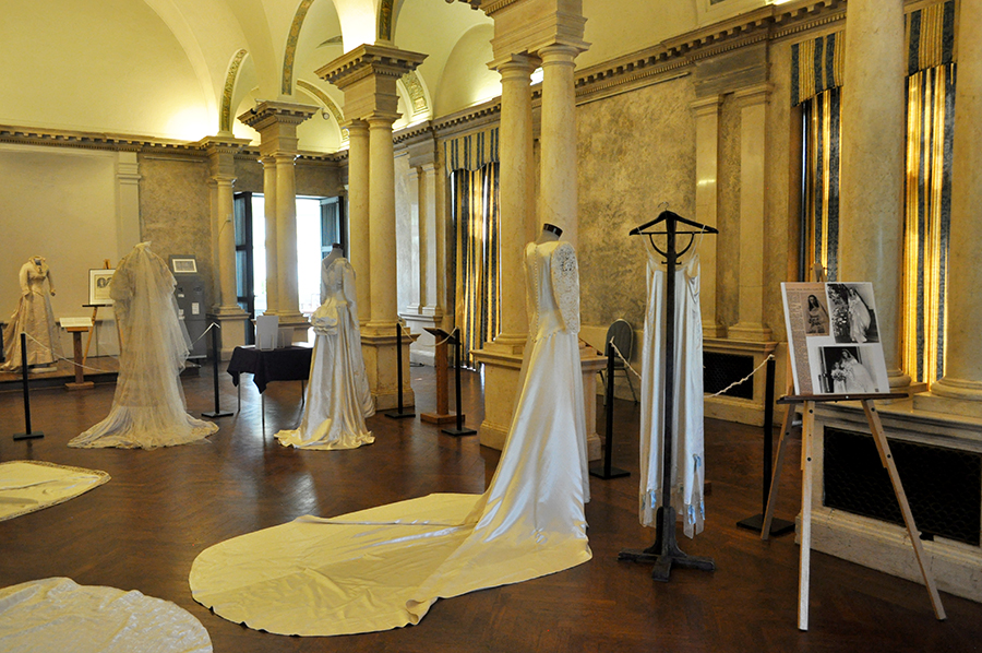 A Big Marble Hall With Columns Has Several Wedding Gowns On Display, The Foreground Shows A Five Foot Train Spread On The Parquet Floor