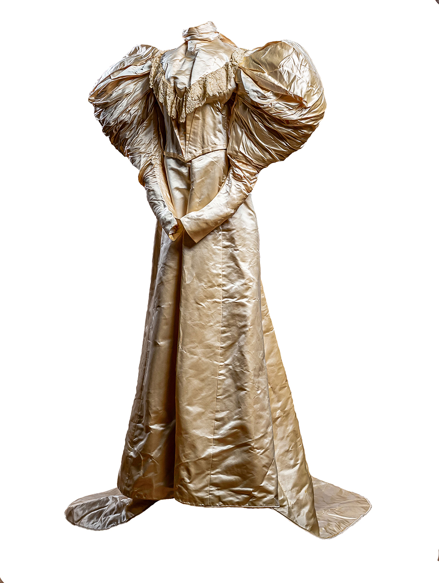 Two-piece suit of candlelight ivory silk satin. The bodice is boned with a high neckline; leg-of-mutton ruffled sleeves; very full skirt.