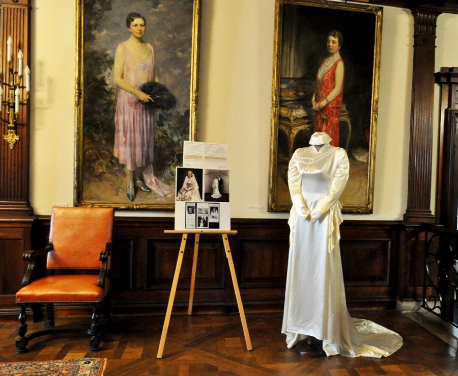A White Silk Wedding Gown With A Smal Train And A Headpiece Are In Display Infront Of The Portraits Of Katharine And Belle Skinner