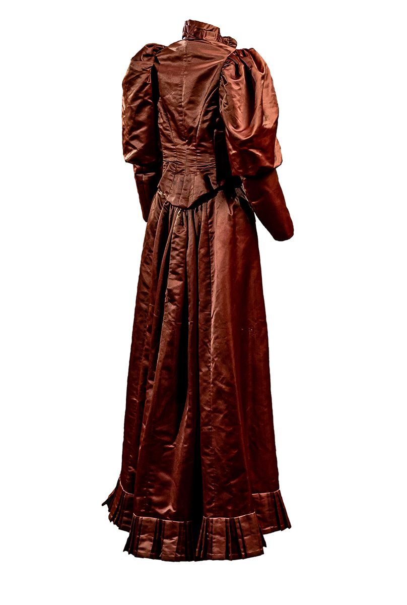 Back of red brown wedding suit Jacket is fitted and boned with gem-like metal buttons; leg-of-mutton sleeves; fitted styling. Skirt has box-pleat trim at the hem and darting. Collar is adorned with decorative flowers and closes with a hook and eye.