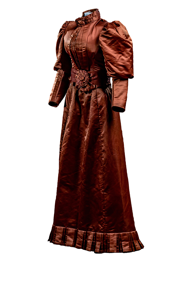 Front of red-brown wedding suit. Jacket is fitted and boned with gem-like metal buttons; leg-of-mutton sleeves; fitted styling. Skirt has box-pleat trim at the hem and darting. Collar is adorned with decorative flowers and closes with a hook and eye.