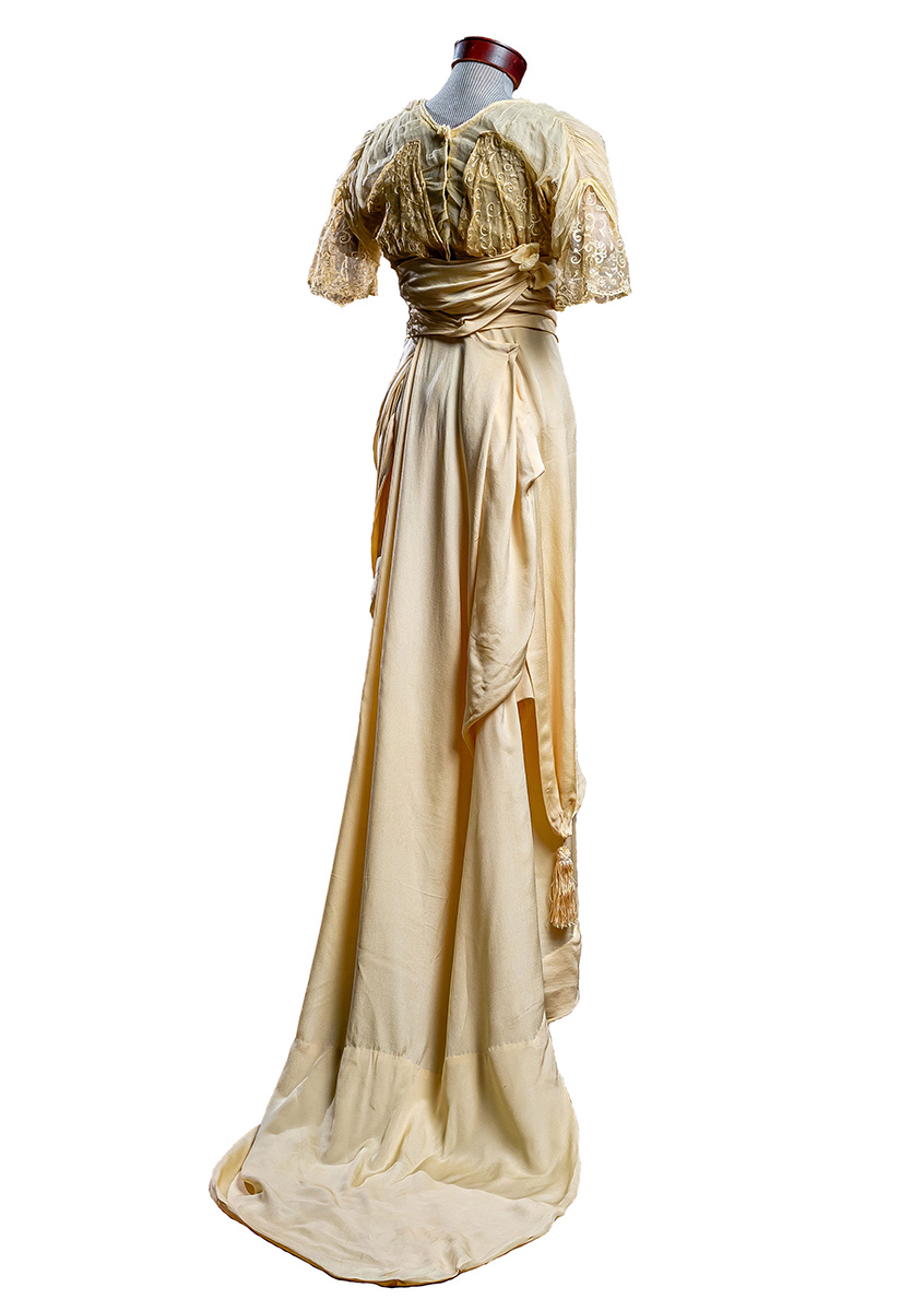 back of Apricot crepe silk with sheer layered yoke and capped sleeves. Layered wrap skirt with short, weighted train. Tassel ornamentation.