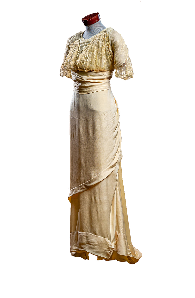 Apricot crepe silk with sheer layered yoke and capped sleeves. Layered wrap skirt with short, weighted train. Tassel ornamentation.