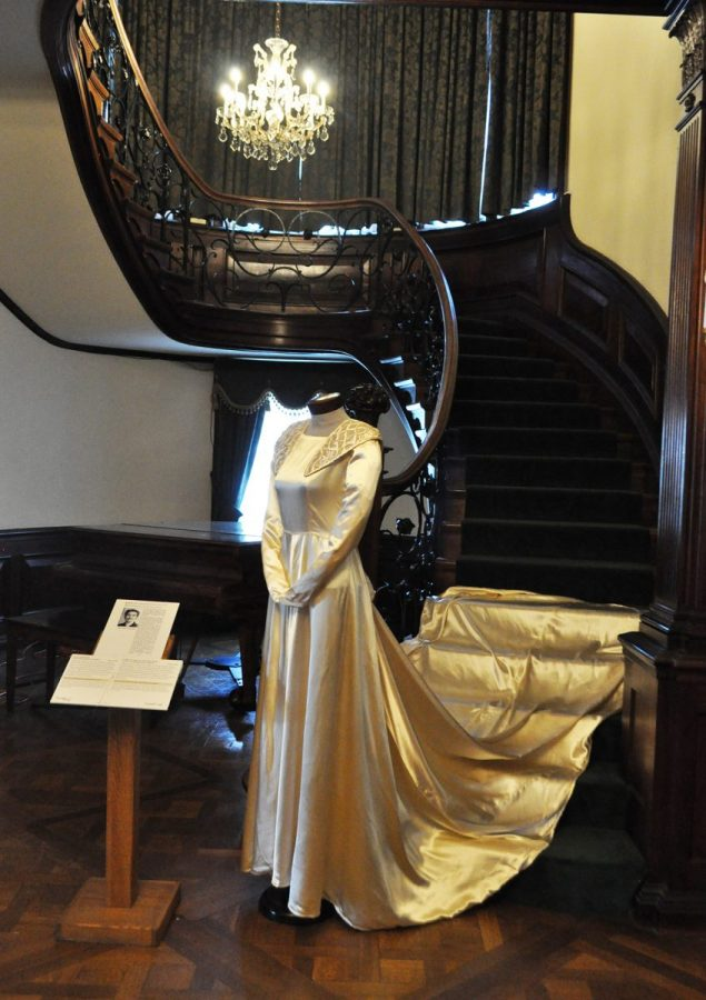 An Ivory Skilk Gown With A Long Train Is On Display In Front Of A Grant, Curved Staircase With A Green Carpet. A Small Chandelier Glows Above