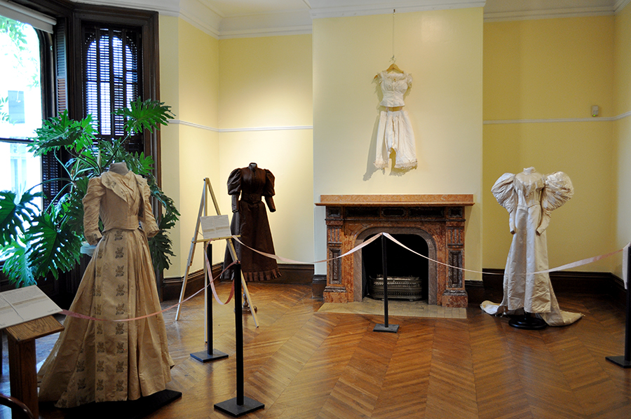 Wedding Gowns Of Various Colors, Ivory, White, Brown, And Cream, On Display In A Yellow Gallery With A Set Of Old Fashioned Under Garments Hanging Above A Pink Marble Fireplace