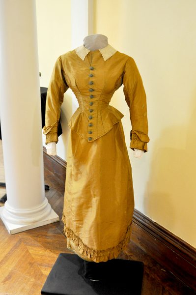 An Old Fashioned Yellow Wedding Outfit With Tightly Cinched Bodice And Silk Skirt With A Ruffled Hem. Long Sleeves And White Collar On The Dress